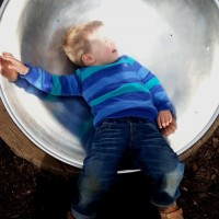 boy in metal bowl playground equipment